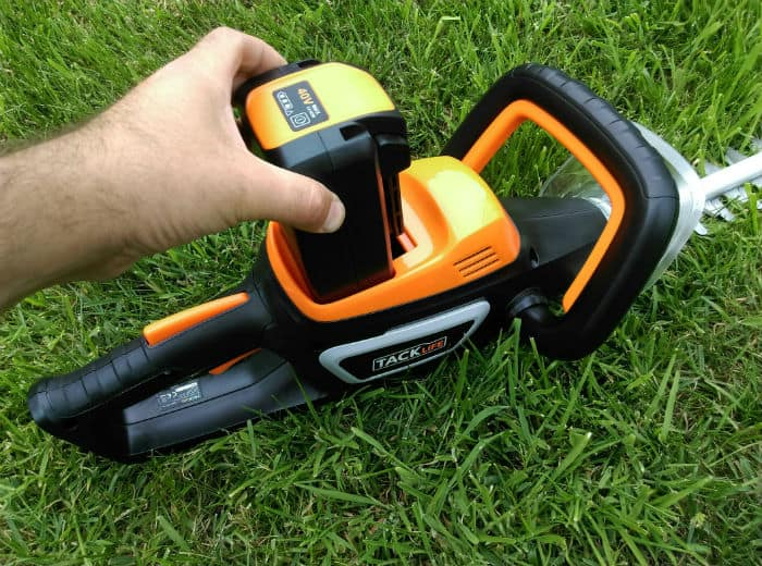Battery being inserted into TackLife Cordless Hedge Trimmer